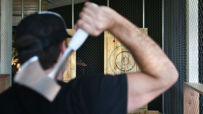 Adam Schilling, co-owner of Maniax, gets ready to throw an axe at one of the targets.