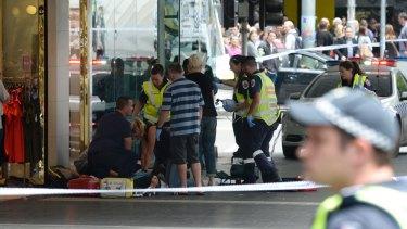 Ambulance paramedics treat an injured pedestrian on Bourke Street.