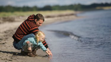2.5 year old toddler enjoying the late summer at the beach with her dad. generic outdoors nature father young daughter dad girl