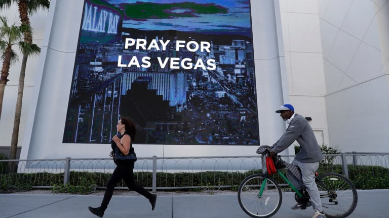 People travel past a sign honoring the victims of a mass shooting in Las Vegas.