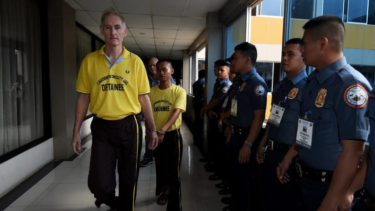 Peter Scully (left) arrives at the Cagayan De Oro court handcuffed to another inmate on his first day of his trial.