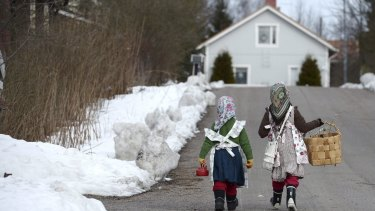 Two girls walks towards a house, in Jarvenpaa, Finland.