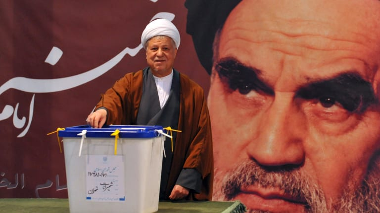 Ali Akbar Hashemi Rafsanjani casts his ballot for parliamentary elections in front of a portrait of  Ayatollah Khomeini in 2012.