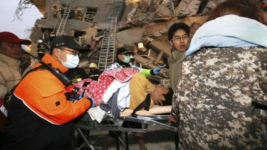 Rescue workers carry a man from the site of a toppled building in Tainan, Taiwan.