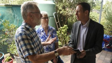 Lainie and David Shorthouse showing their Reposit Power solar battery storage data to Minister Shane Rattenbury MLA.