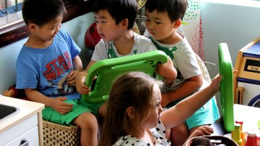 Children at the Top Ryde Early Learning centre using a new language app on a tablet.
