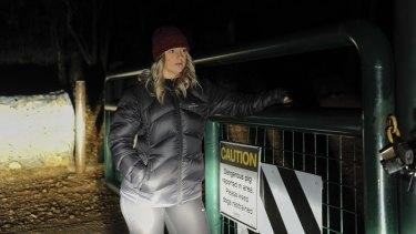 Michaela Vodvarka at Mount Jerrabomberra on Monday night near a sign  warning of a dangerous pig 00b05244341