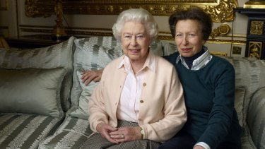 The Queen's only daughter Princess Anne sitting with her arm wrapped protectively around her mother.