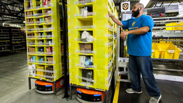 An Amazon staff member picks items from a rack brought to him by a Kiva robot.