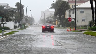 A car makes its way up a flooded street in Jacksonville Beach, Florida.