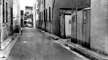 The body of Frank McLean, William Macdonald's third victim, was found in the gutter in front of the gates in the right foreground of this picture of Little Bourke Street, Darlinghurst, on a Saturday night in 1962.