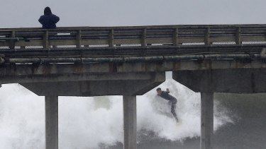 A California surfer catches waves during a winter storm.