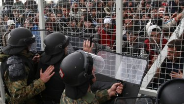 Stranded refugees and migrants try to break an iron fence from the Greek side of the border as Macedonian policemen push them back, near Gevgelija on Monday.