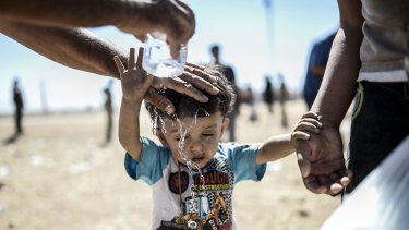 Cooling down: A Syrian Kurd pours water on a child after they crossed the border between Syria and Turkey in September, fleeing from Islamic State fighters who advanced into their villages.