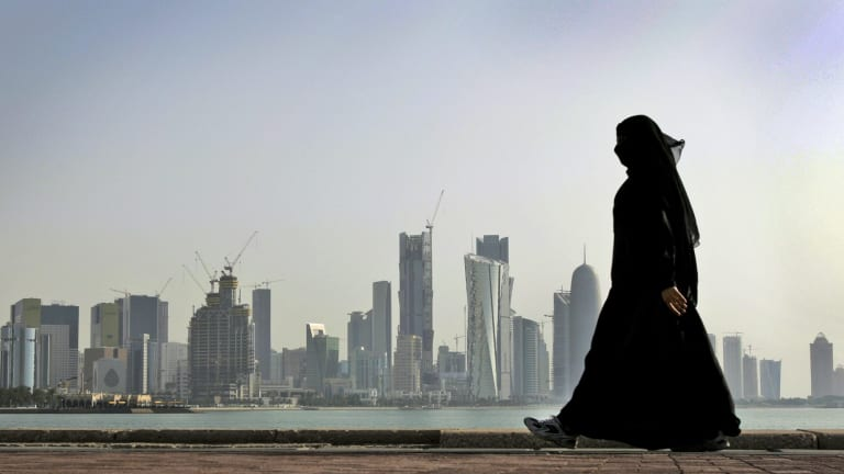 A Qatari woman walks in front of the city skyline in Doha. .