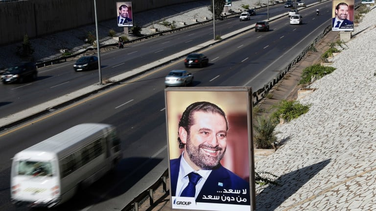 """Posters showing Lebanese Prime Minister Saad Hariri with Arabic that reads, """"No happiness without you Saad,"""" hang along the airport highway, in Beirut."""