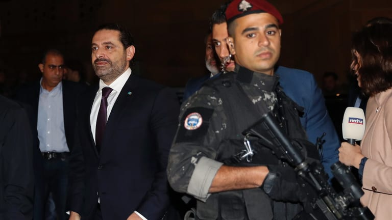 Lebanese Prime Minister Saad Hariri, left, walks to pray over his father's grave.