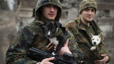 Ukrainian servicemen put their dogs under their jackets to stay warm in Mariupol in January.