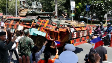 A convoy of Philippine Marines, who took part in the battle against Muslim militants in the besieged city of Marawi in southern Philippines, are given a heroes welcome as they pass by the Philippine Navy headquarters.
