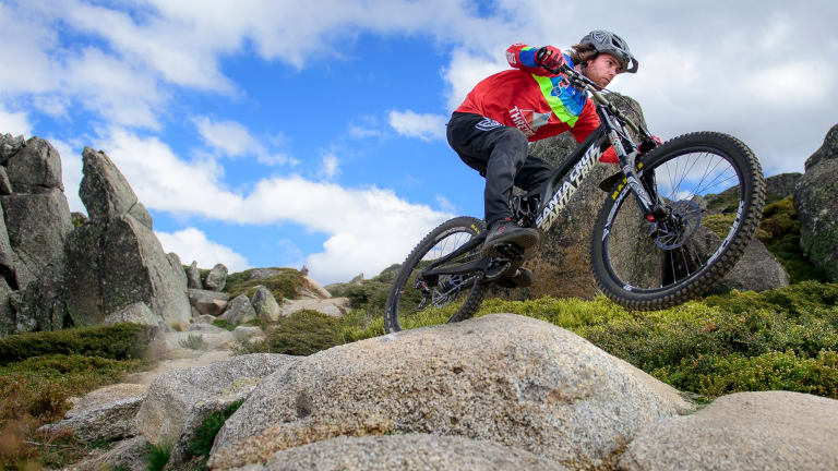 Tim Windshuttle hits a jump with speed on Thredbo's All-Mountain Trail.