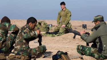 Australian soldier Corporal Emmette Taylor teaches Iraqi personnel how to strip an assault rifle at the Taji military complex.