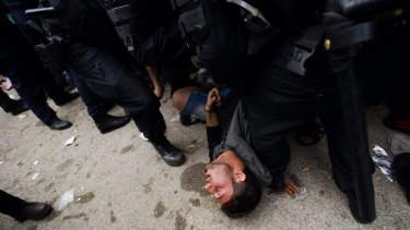 A migrant collapses from exhaustion next to Croatian police officers close to the border with Serbia.