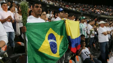 Fans of Colombia's Atletico Nacional soccer team hold flags from Brazil and Colombia during a tribute to Chapecoense where the teams were to face each other in Medellin, Colombia.
