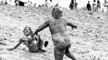 Sunbury turned to Mudbury in 1975 as the rain teemed down. Mudslider John Akers, 18, of Frankston bears down on Brian Carson of Bonbeach during the  washout.