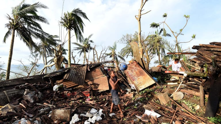 A boy plays with a ball as his mother searches through the ruins of their family home in Port Vila, Vanuatu.