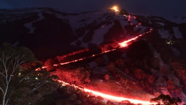 300 skiers conduct a flare run on the mountain at the Thredbo Alpine Village on Saturday, July 29, 2017. Eighteen people died when the Bimbadeen and Carinya Lodges were destroyed at Thredbo Alpine Village at 11:35 pm on Wednesday, July 30, 1997.