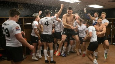 Off to a great start: Toronto Wolfpack players celebrate in the locker room after their 62-12 win over Oxford in their inaugural home game in League 1.