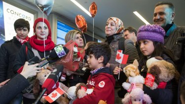 Tima Kurdi, third from left, meets her brother, Mohammad Kurdi, right, and his family, who have escaped conflict in Syria, at Vancouver International Airport.