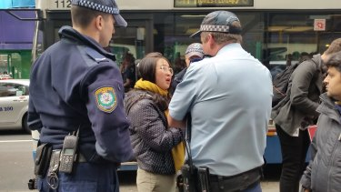 Police question a young woman outside the Sydney Apple Store.