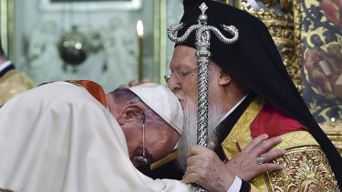 Ecumenical Patriarch Bartholomew I, right, kisses Pope Francis' head during an ecumenical prayer at the Patriarchal Church of St George in Istanbul in 2014.
