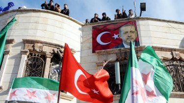 Turkey-backed Free Syrian Army fighters stand on the roof of a building with a poster of Turkey's President Recep Tayyip Erdogan.