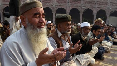 Pakistani Muslims pray for children and teachers killed by Taliban militants in the school attack.