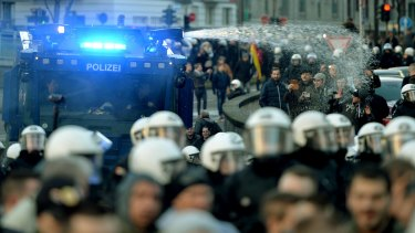 Police drive back right-wing demonstrators using a water cannon during protests in Cologne.