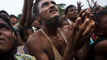 A Rohingya man stretches his arms out for food distributed by local volunteers