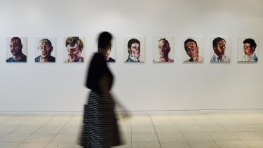 A woman walks past a series of paintings of the Bali Nine by Myuran Sukumaran that are a part of the <I>Another Day in Paradise</I> exhibition.