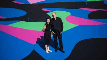 Architect and arts patron Corbett Lyon with his wife Yueji standing on Reko Rennie's <i>Visible Invisible</i>, painted on the base of his second Housemuseum of contemporary art in Kew.
