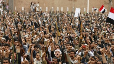 Houthi rebels hold up their weapons in the Yemeni capital, Sanaa.