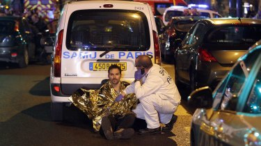 A medic tends to a man near the Boulevard des Filles-du-Calvaire.
