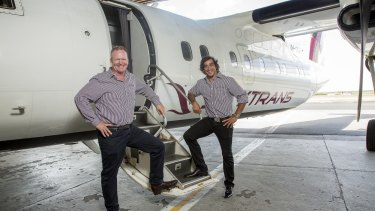 Skytrans co-owner Peter Collings with footballer and shareholder Johnathan Thurston in front of a Dash-8.