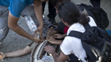 A man gets medical help after he was injured while trying to push through a police line in Tovarnik, Croatia on Thursda. More than 2000 men, women and children were stuck at the local train station