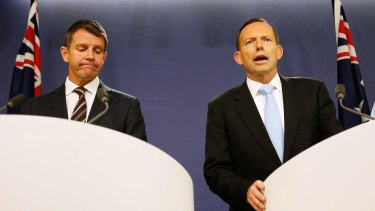 The re-election chances of the government of NSW Premier Mike Baird, left, are being eroded by the unpopularity of Prime Minister Tony Abbott.