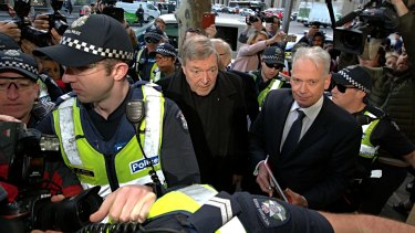 Cardinal George Pell makes his way through the throng of media, with lawyer Paul Galbally by his side.