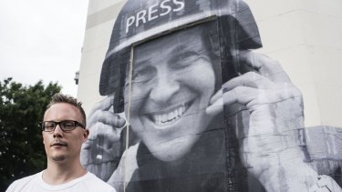 Street artist Hego with a paste up he did of jailed Journalist Peter Greste.