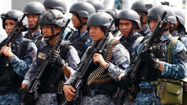 An armed Philippine coast guard unit leave the liberated Marawi late last year.