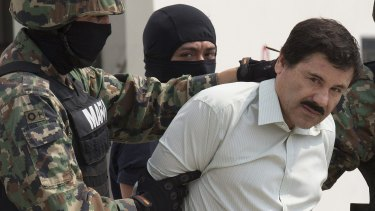 "Mexican drug trafficker Joaquin ""El Chapo"" Guzman is escorted by security forces after his capture. Mexican drug cartels are beginning to move into Australia."