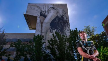 Strike a pose: artist Guido van Helten with his mural of deaf dancer, Anna Seymour.